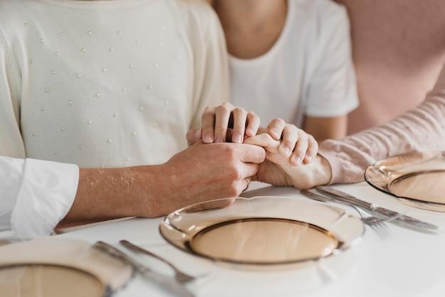 Familie betet, während sie ihre hände hält