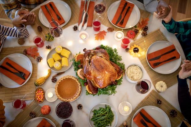 Familie betet zusammen vor dem thanksgiving-dinner
