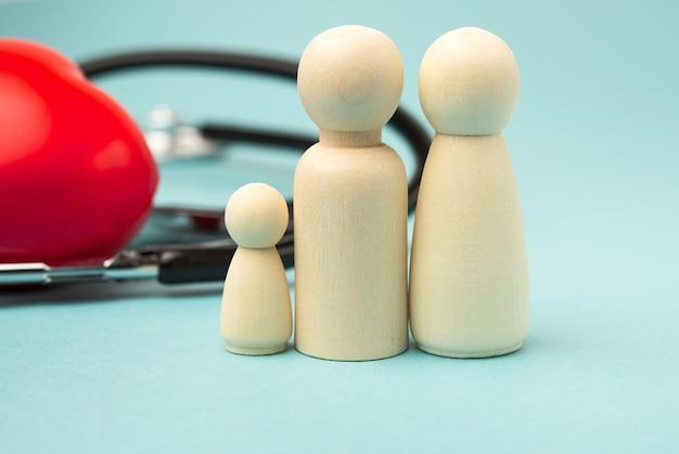 Familie der hölzernen figuren der männer auf hintergrund des roten herzens und des stethoskops, krankenversicherungskonzept, schließen oben