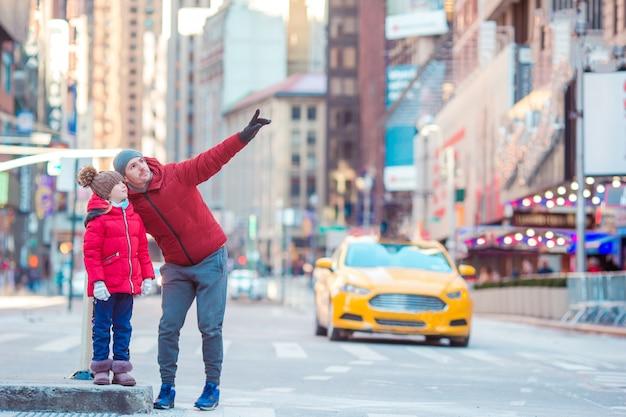 Familie des vaters und des kleinkindes auf times square während ihrer ferien in new york city