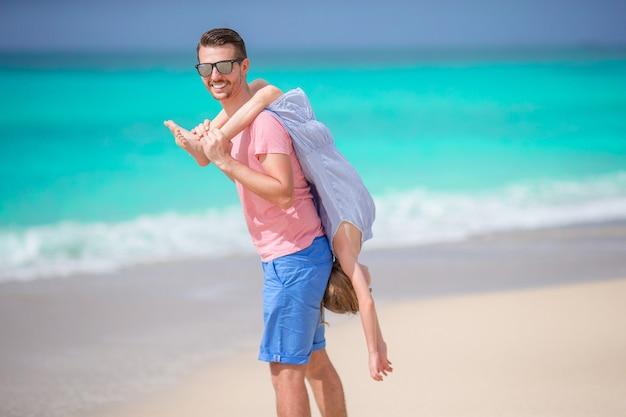 Familie des vaters und des sportlichen kleinen mädchens, die spaß auf dem strand haben