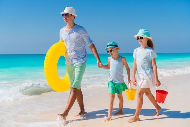 Familie des vatis und der kinder, die auf weißen tropischen strand auf karibikinsel mit strand gehen, spielt. familienurlaub am strand