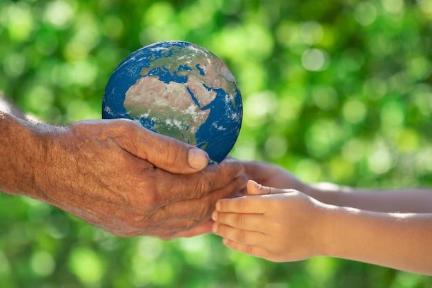 Familie, die 3d-planeten in den händen gegen grüne unscharfe oberfläche hält