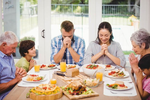 Familie, die am speisetische sitzt und zusammen vor mahlzeit betet
