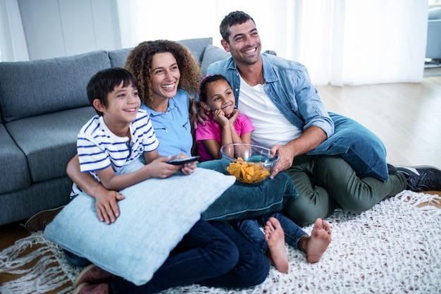 Familie, die amerikanisches fußballspiel im fernsehen aufpasst