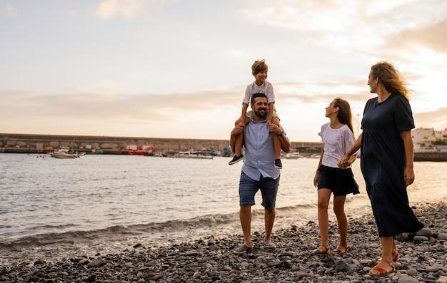 Familie, die an einem tag ihres urlaubs bei sonnenuntergang am strand spazieren geht