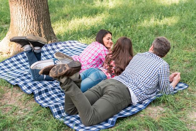 Familie, die auf blauer karierter decke über gras im garten liegt