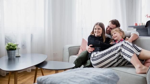 Familie, die auf couch sich entspannt