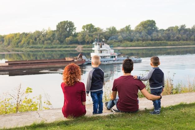 Familie, die auf dem grünen grund sitzt und klein betrachtet