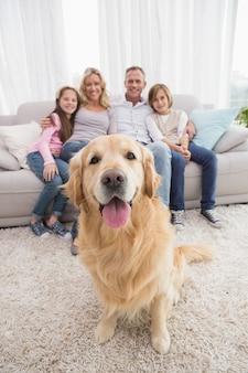 Familie, die auf der couch mit golden retriever im vordergrund sitzt