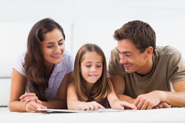Familie, die auf einem teppich mit einem buch liegt