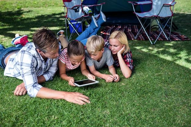 Familie, die auf gras liegt und digitale tablette verwendet