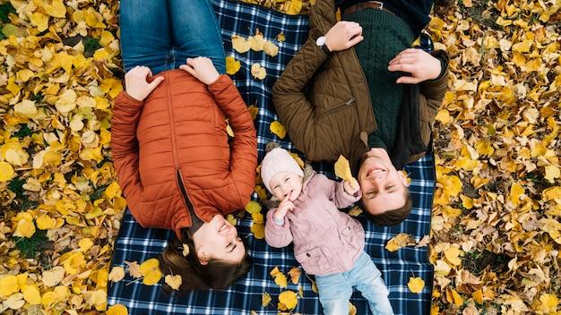 Familie, die auf herbstblättern im park sich entspannt