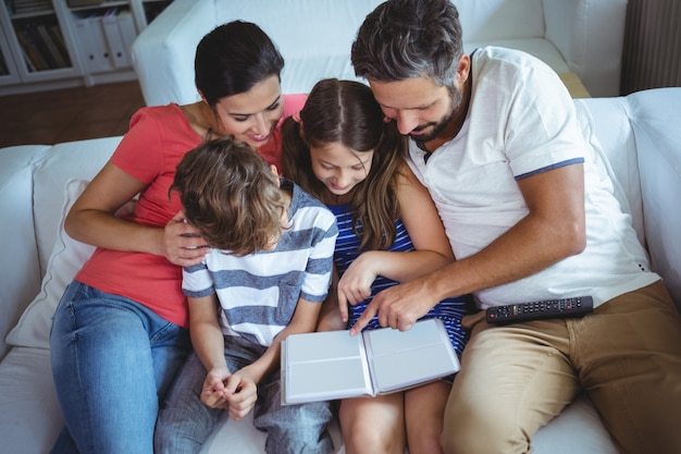 Familie, die auf sofa sitzt und ein fotoalbum betrachtet