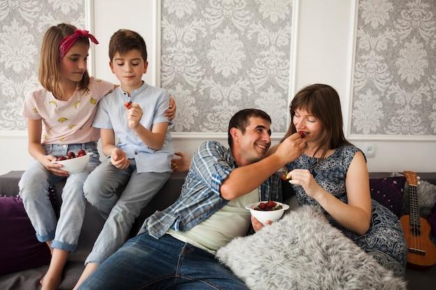Familie, die auf sofa sitzt und zu hause erdbeere genießt