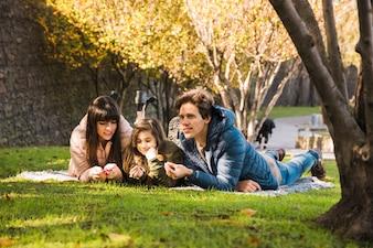 Familie, die auf Wolldecke im Park liegt