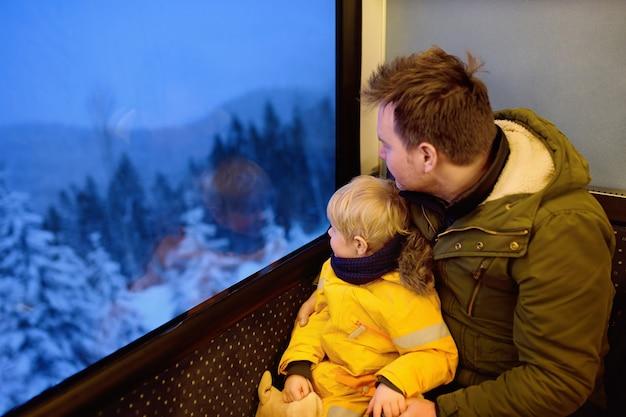 Familie, die aus dem fenster des zugs heraus während der reise auf zahnradbahn / zahnradbahn in den alpenbergen schaut