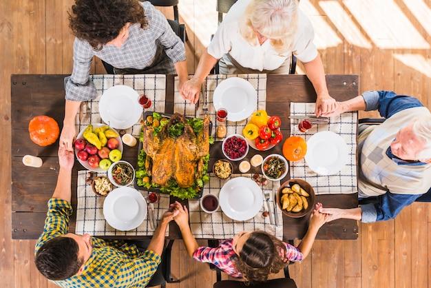 Familie, die bei tisch mit händchenhalten sitzt