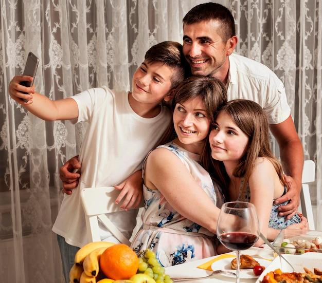 Familie, die beim abendessen selfie zusammen nimmt