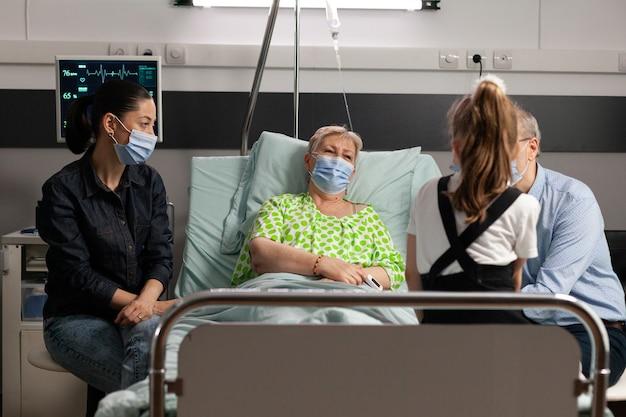 Familie, die beim besuch der kranken großmutter eine schutzmaske gegen covid trägt