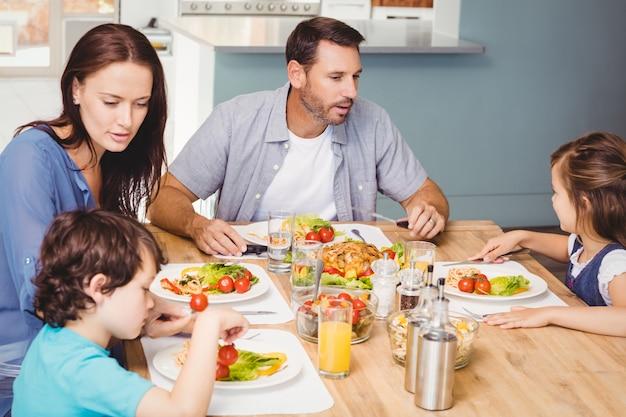 Familie, die beim sitzen am speisetische zu mittag isst