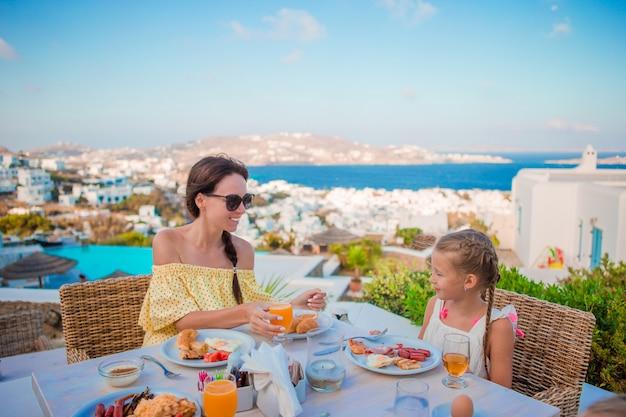 Familie, die café am im freien mit erstaunlicher ansicht über mykonos-stadt frühstückt. entzückendes mädchen und mutter, die frischen saft trinkt und hörnchen auf luxushotelterrasse isst