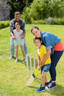 Familie, die cricket im park spielt