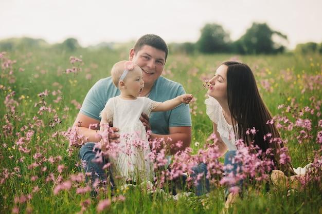 Familie, die das leben zusammen im sommerfeld mit wilden blumen genießt.