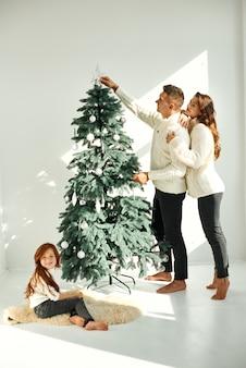 Familie, die den weihnachtsbaum zu hause schmückt