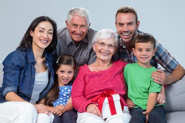 Familie, die der großmutter ein geschenk gibt