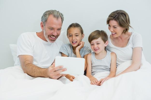 Familie, die digitales tablett auf bett im schlafzimmer zu hause verwendet