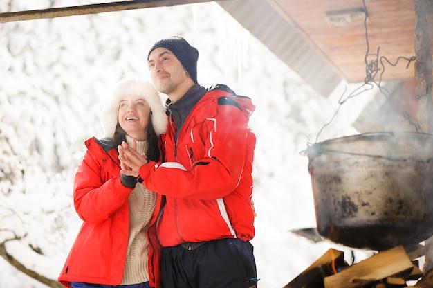 Familie, die draußen abendessen im winter kocht. lagerfeuer, grill, bowler.