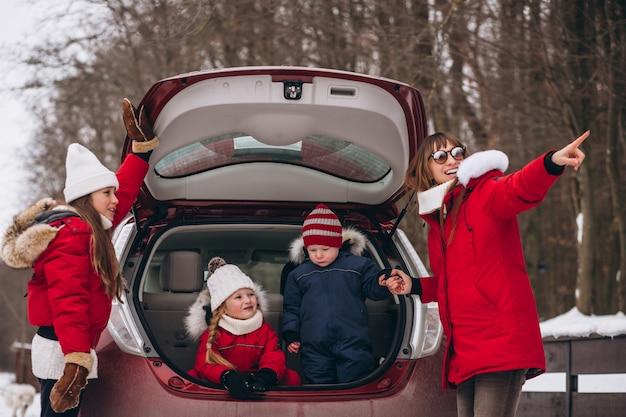 Familie, die draußen auf der rückseite des autos im winter sitzt