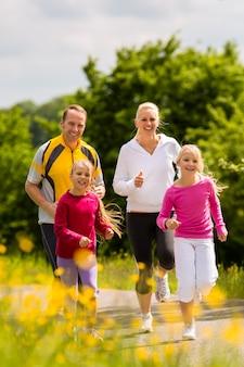 Familie, die draußen für sport mit den kindern am sommertag rüttelt