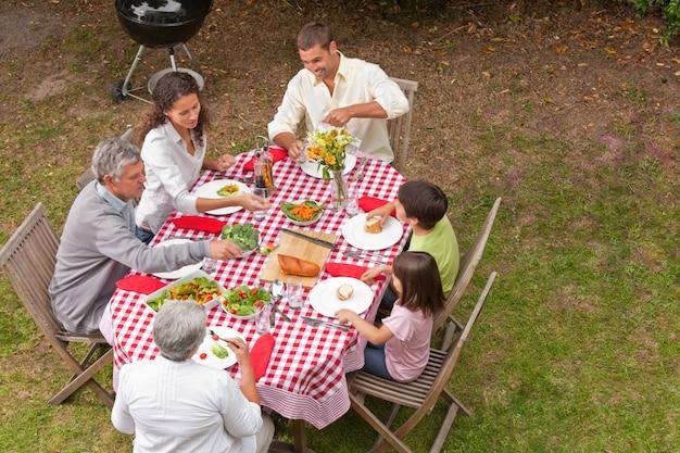 Familie, die draußen im garten isst