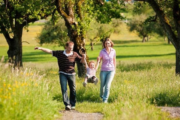 Familie, die draußen im sommer einen spaziergang macht und ihren kleinen sohn auf spielerische weise in die luft wirft