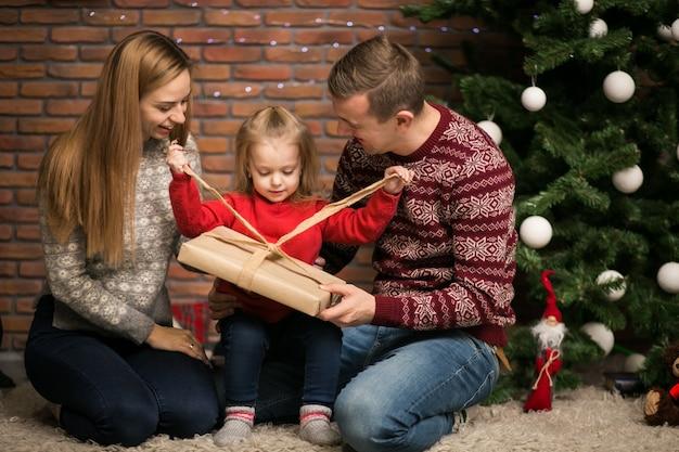 Familie, die durch den weihnachtsbaum mit kleinen tochterverpackungsgeschenken sitzt
