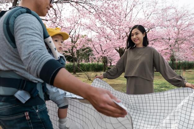 Familie, die ein picknick neben einem kirschbaum hat