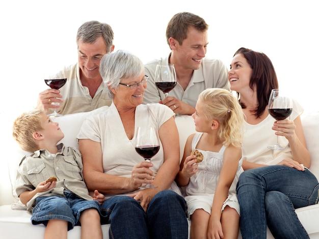 Familie, die eine feier mit wein und keksen isst