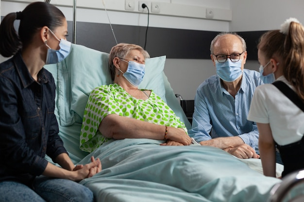 Familie, die eine medizinische gesichtsmaske gegen coronavirus trägt, die kranke großmutter besucht
