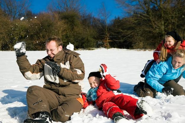 Familie, die eine schneeballschlacht hat