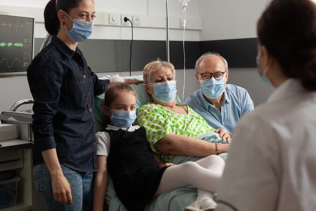 Familie, die eine schützende gesichtsmaske gegen coronavirus trägt, während sie ältere ältere frauen besucht