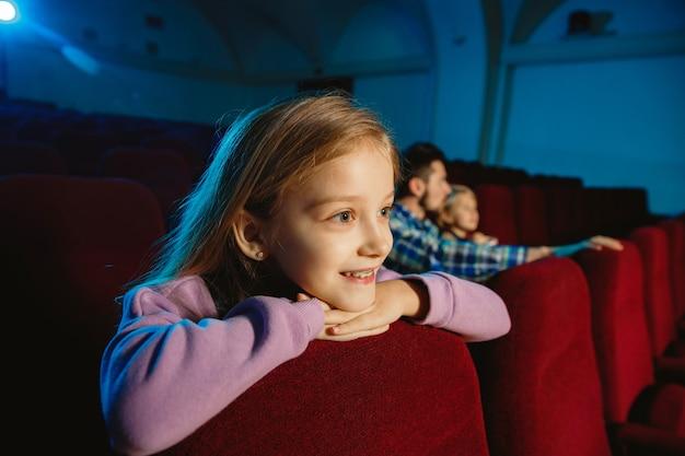 Familie, die einen film in einem kino, haus oder kino sieht