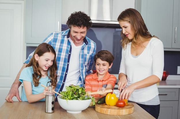 Familie, die einen gemüsesalat zubereitet