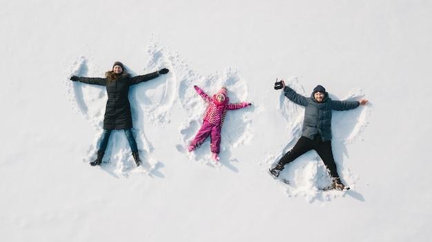 Familie, die einen schneeengel macht. luftaufnahme. mutter und vater und kinder machen einen schneeengel