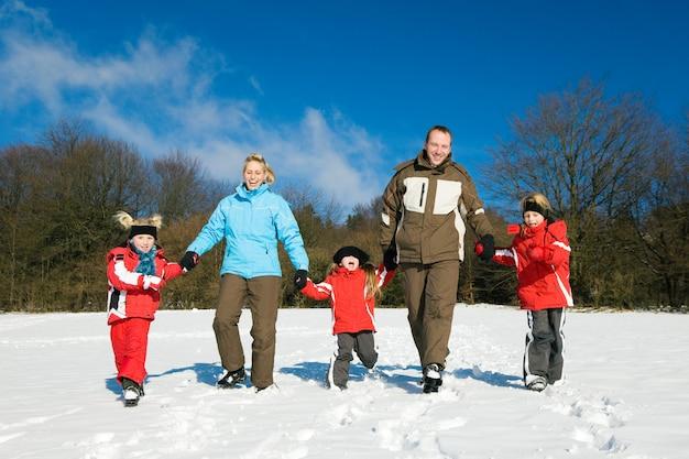Familie, die einen spaziergang im schnee hat