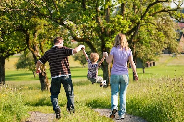 Familie, die einen weg draußen am sommer hat
