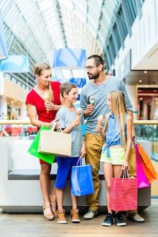 Familie, die eiscreme im einkaufszentrum mit taschen isst