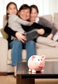 Familie, die geld auf einem sparschwein spart