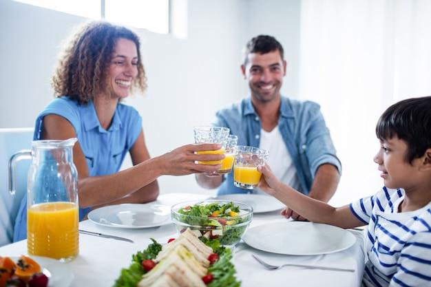 Familie, die gläser orangensaft beim frühstücken röstet